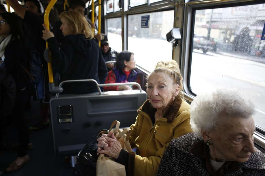 Diane Pechenino (in yellow) rides quietly as MUNI operator Charles Davis, known to many as the singing bus driver, sings the stops on the 29 Sunset in San Francisco, Calif. Photo: Mike Kepka, The Chronicle