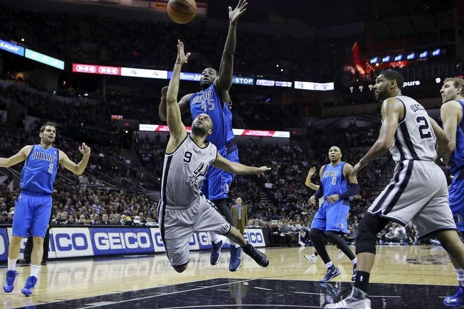 San Antonio Spurs' Tony Parker shoots around Dallas Mavericks' DeJuan Blair during first half action Sunday March 2, 2014 at the AT&T Center. Photo: San Antonio Express-News