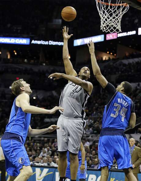 San Antonio Spurs' Boris Diaw shoots between Dallas Mavericks' Dirk Nowitzki (left) and Brandan Wright during second half action Sunday March 2, 2014 at the AT&T Center. The Spurs won 112-106. Photo: San Antonio Express-News