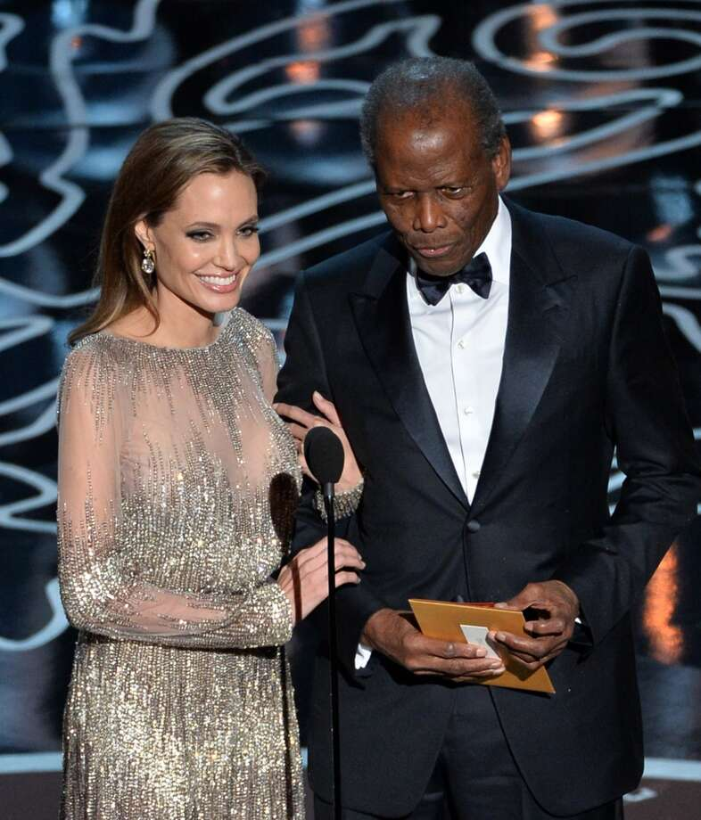 Actors Angelina Jolie (L) and Sidney Poitier walk onstage during the Oscars at the Dolby Theatre on March 2, 2014 in Hollywood, California. Photo: Kevin Winter, Getty Images