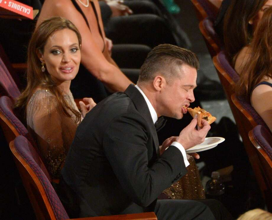 Brad Pitt, foreground, eats pizza as Angelina Jolie, looks on in the audience during the Oscars at the Dolby Theatre on Sunday, March 2, 2014, in Los Angeles. Photo: John Shearer, Associated Press