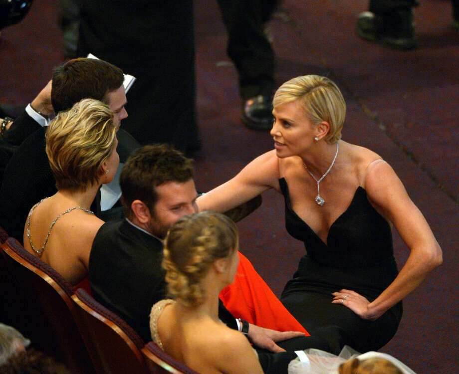 Charlize Theron, right, talks to Jennifer Lawrence in the audience at the Oscars at the Dolby Theatre on Sunday, March 2, 2014, in Los Angeles. Photo: John Shearer, Associated Press