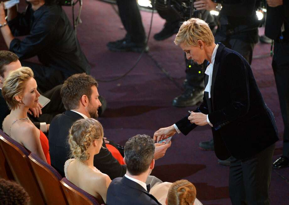 Ellen DeGeneres, right, gives Bradley Cooper a lottery ticket during the Oscars at the Dolby Theatre on Sunday, March 2, 2014, in Los Angeles. Photo: John Shearer, Associated Press