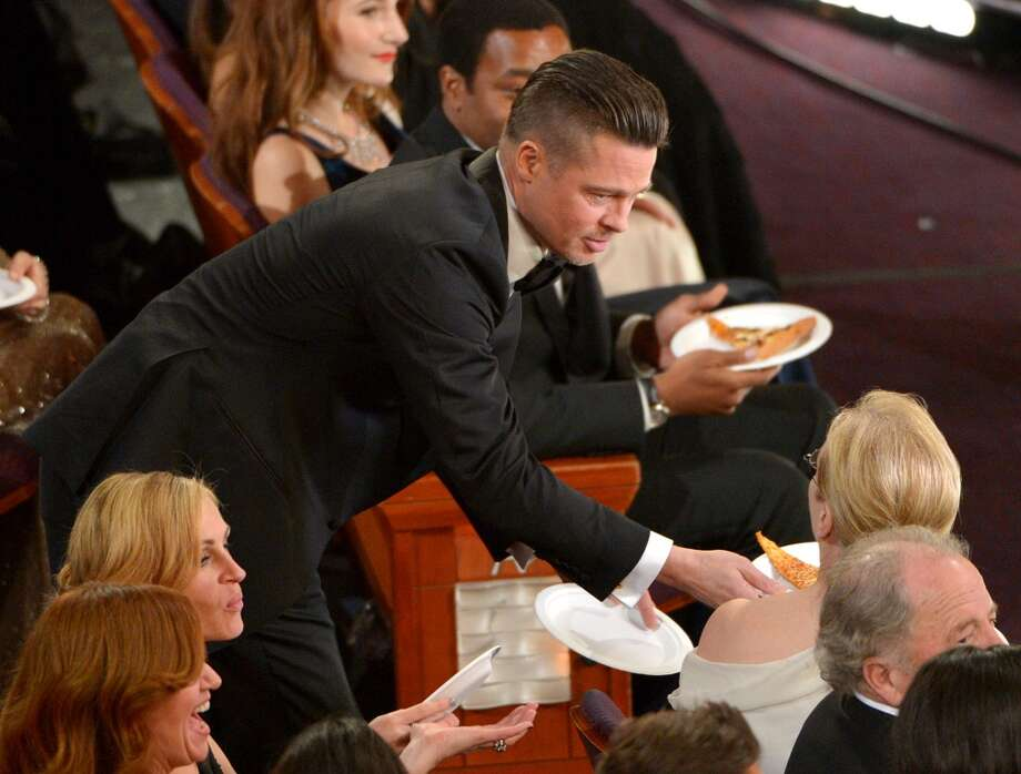 Brad Pitt, left, shares pizza with Meryl Streep in the audience during the Oscars at the Dolby Theatre on Sunday, March 2, 2014, in Los Angeles. Photo: John Shearer, Associated Press