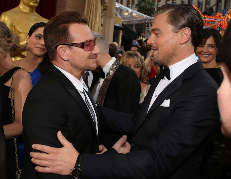 Bono, left, and Leonardo DiCaprio speak as they arrive at the Oscars on Sunday, March 2, 2014, at the Dolby Theatre in Los Angeles. Photo: Matt Sayles, Associated Press