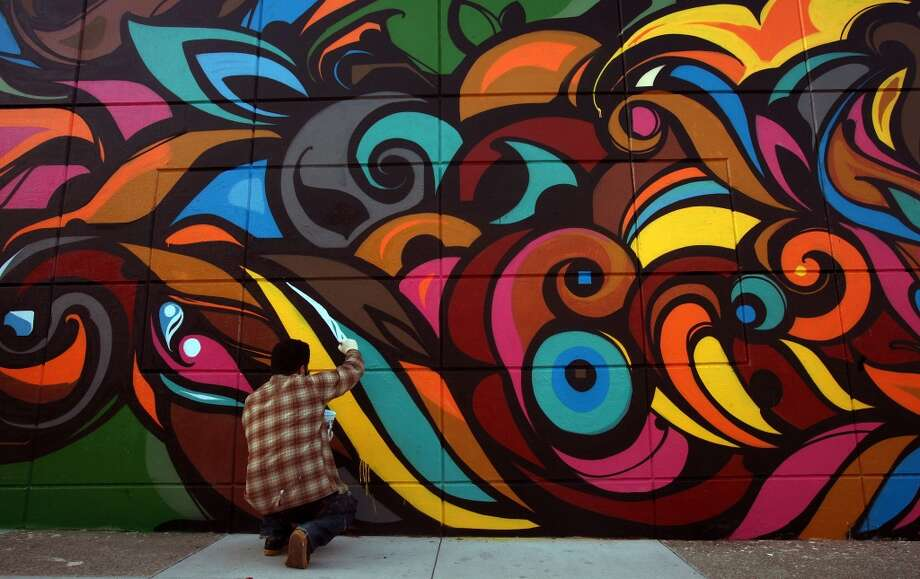 We'd like to argue that graffiti replaced by organized street murals is one of the more beautiful early signs of gentrification.  Pictured: Victor Reyes working on his mural at 23rd and Mission streets on a Walgreens in San Francisco on April 16, 2010. Photo: Liz Hafalia, The Chronicle