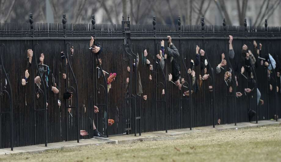 Several hundred students and youth who marched from Georgetown University to the White House to protest the Keystone XL Pipeline tied themselves to the fence outside the White House in Washington, Sunday, March 2, 2014. Many of those protesting were arrested. (AP Photo/Susan Walsh) Photo: Susan Walsh, ASSOCIATED PRESS