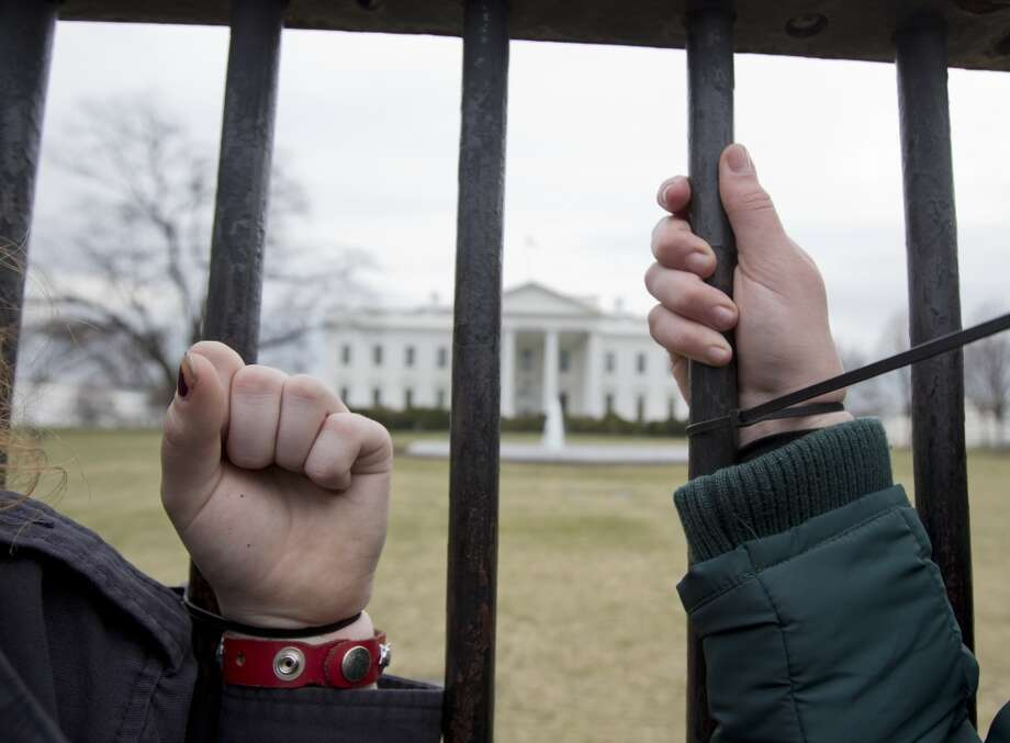 Protestors are strapped to the White House fence in Washington, during a protest against the proposed Keystone XL oil pipeline, Sunday, March 2, 2014. They were later arrested. (AP Photo/Manuel Balce Ceneta) Photo: Manuel Balce Ceneta, ASSOCIATED PRESS