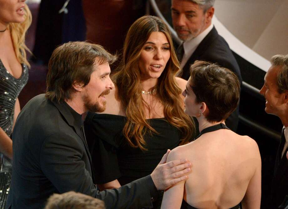 Christian Bale, left, and his wife Sibi Blazic, talk with Anne Hathaway, right, in the audience at the Oscars at the Dolby Theatre on Sunday, March 2, 2014, in Los Angeles. Photo: John Shearer, Associated Press