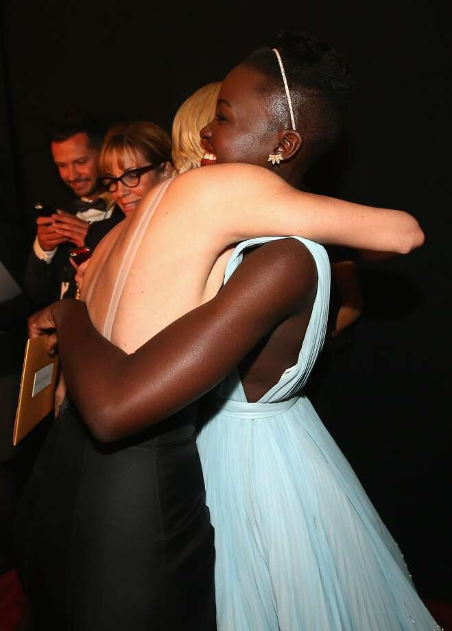 Charlize Theron and Lupita Nyong'o meet backstage during the Oscars held at Dolby Theatre on March 2, 2014 in Hollywood, California. Photo: Christopher Polk, Getty Images