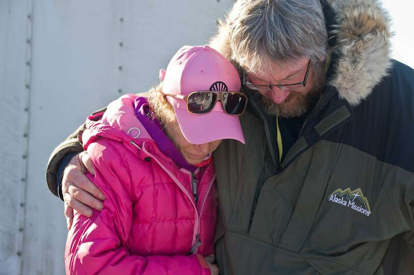 Musher DeeDee Jonrowe prays with Scott Jenkins of Alaska Missions before the start of the Iditarod T