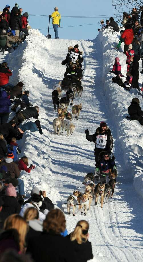 Scott Janssen of Anchorage, Alaska, top, catches up to Allen Moore of Two Rivers, Alaska, on the Cordova Street hill during the ceremonial start for the 2014 Iditarod Trail Sled Dog Race on Saturday, March 1, 2014, in Anchorage, Alaska. (AP Photo/The Anchorage Daily News, Erik Hill)  LOCAL TV OUT (KTUU-TV, KTVA-TV) LOCAL PRINT OUT (THE ANCHORAGE PRESS, THE ALASKA DISPATCH) Photo: Erik Hill, Associated Press