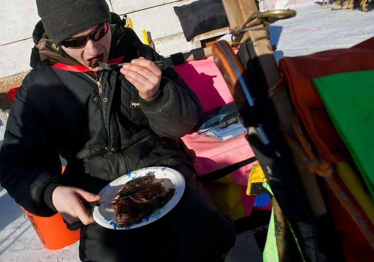 Musher Wade Marrs eats a large ribeye steak before racing begins on the Iditarod Trail Sled Dog Race