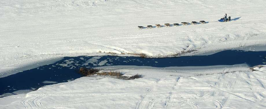 A musher drives his dog team past some open water just after the start of the 2014 Iditarod Trail  Sled Dog Race out of Willow, Alaska, Sunday, March 2, 2014. The race will take mushers nearly a thousand miles to the finish line in Nome, on Alaska's western coast. (AP Photo/Anchorage Daily News, Bob Hallinen) Photo: Bob Hallinen, Associated Press