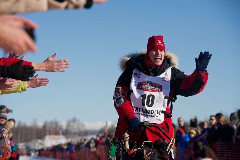 Aliy Zirkle waves to fans during the Iditarod Trail Sled Dog Race in Willow Lake, Alaska, on Sunday,