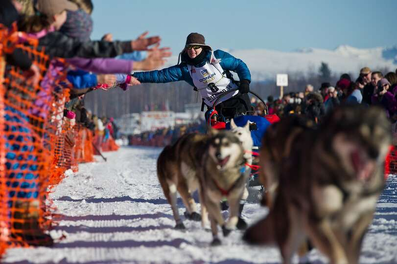 Musher Yvonne Dabakk greets fans of the Iditarod Trail Sled Dog Race in Willow Lake, Alaska, on Sund