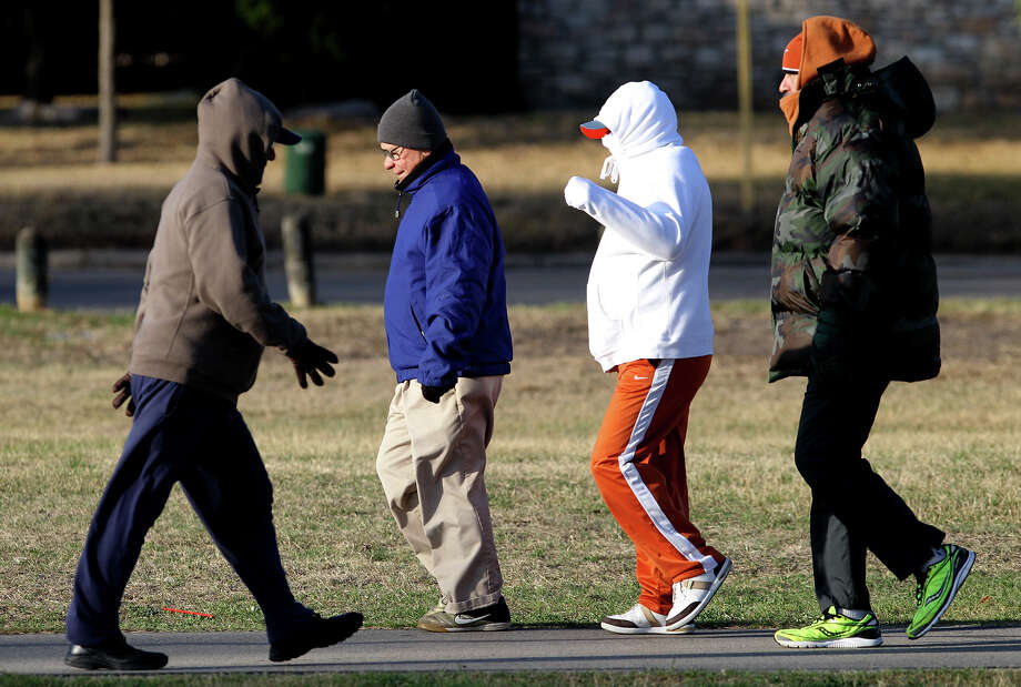 Walkers at Woodlawn Lake are bundled up Monday March 3, 2014 for the morning's chilly temperatures. Monday morning's temperatures were in the lower 30s and there is a chance of rain Monday night. Photo: JOHN DAVENPORT, SAN ANTONIO EXPRESS-NEWS / ©San Antonio Express-News/Photo may be sold to the public