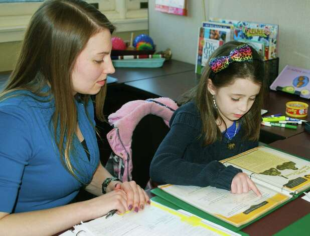 Jessic Reis, owner and director of Reis Learning Center sitting with a student.