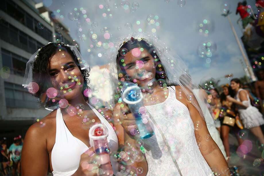 Revelers pose blowing bubbles during the 'Simpatia e Quase Amor' street carnival bloco along Ipanema Beach on March 2, 2014 in Rio de Janeiro, Brazil. Carnival is the grandest holiday in Brazil, annually drawing millions in raucous celebrations. Photo: Mario Tama, Getty Images