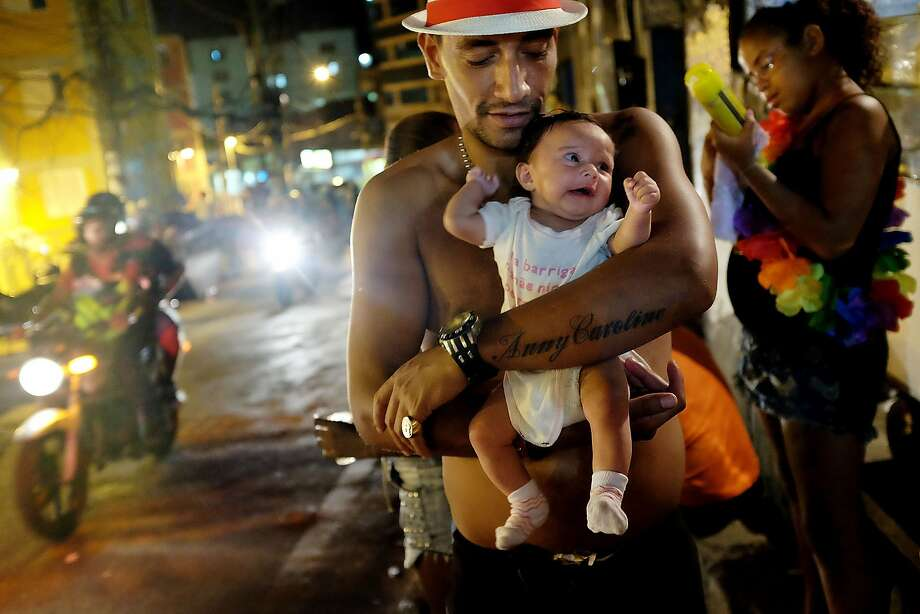 A father poses holding his baby Anny Caroline, tattooed on his arm, during a street carnival bloco in the Rocinha community, or favela, on March 2, 2014 in Rio de Janeiro, Brazil. Carnival is the grandest holiday in Brazil, annually drawing millions in raucous celebrations. Photo: Mario Tama, Getty Images
