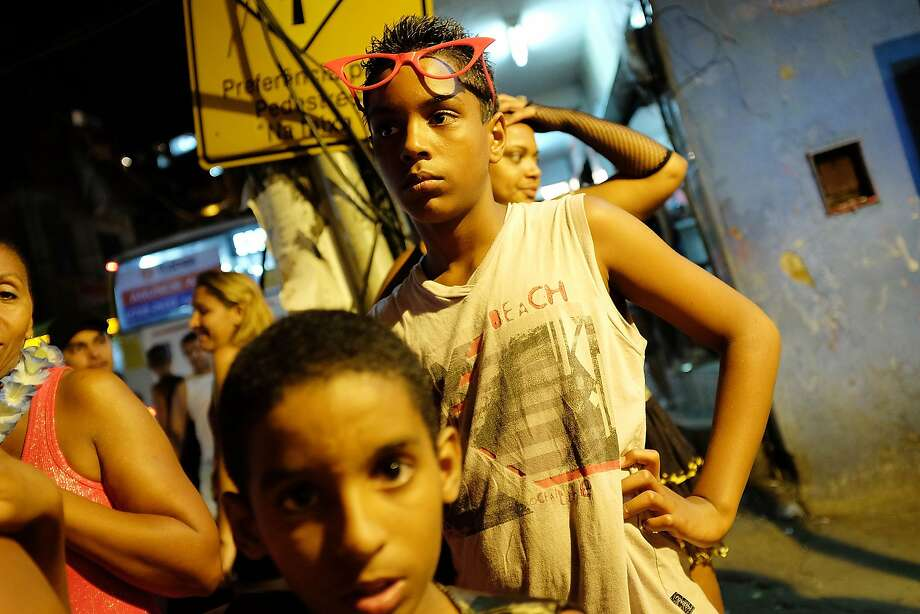 Revelers look on during a street carnival bloco in the Rocinha community, or favela, on March 2, 2014 in Rio de Janeiro, Brazil. Carnival is the grandest holiday in Brazil, annually drawing millions in raucous celebrations.  Photo: Mario Tama, Getty Images