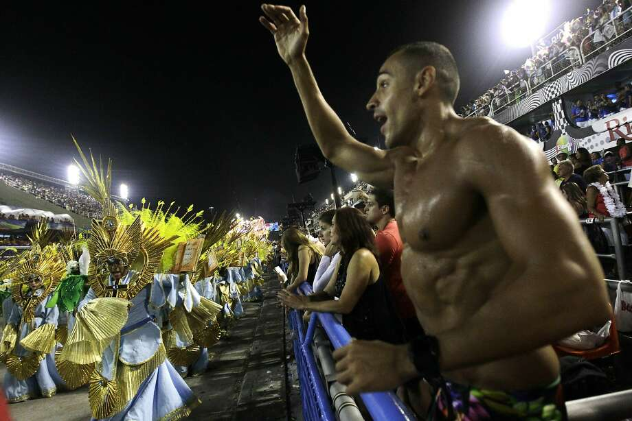 People watch the Sao Clemente samba school parade during carnival celebrations at the Sambadrome in Rio de Janeiro, Brazil, Monday, March 3, 2014. (AP Photo/Silvia Izquierdo) Photo: Silvia Izquierdo, Associated Press