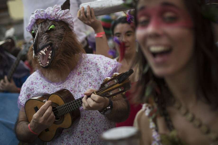 "Dressed as The Big Bad Wolf from the fairytale Little Red Riding Hood, a reveler strums a cavaquinho, a small four-stringed guitar, at the Heaven on Earth block party during Carnival celebration in Rio de Janeiro, Brazil, Saturday, March 1, 2014. Rio's over-the-top Carnival is the highlight of the year for many local residents. Hundreds of thousands of merrymakers will take to the streets in the nearly 500 open-air ""bloco"" parties. (AP Photo/Felipe Dana) Photo: Felipe Dana, Associated Press"