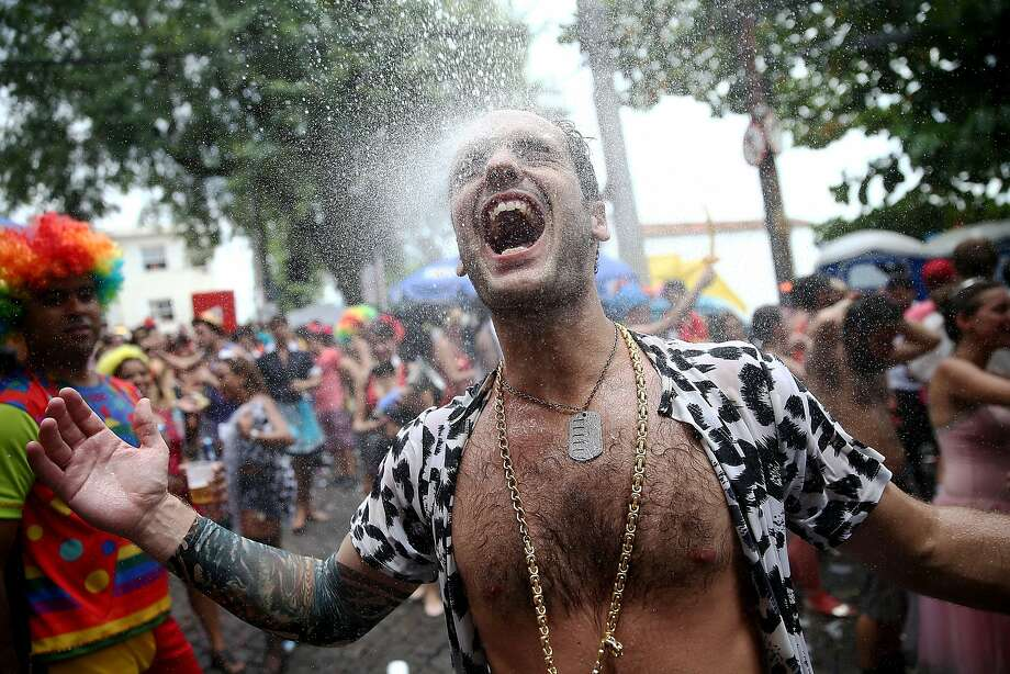 A reveler exalts while being sprayed by water from a resident during the 'Ceu na Terra' street carnival bloco on March 1, 2014 in Rio de Janeiro, Brazil. Carnival is the grandest holiday in Brazil, annually drawing millions in raucous celebrations. Photo: Mario Tama, Getty Images