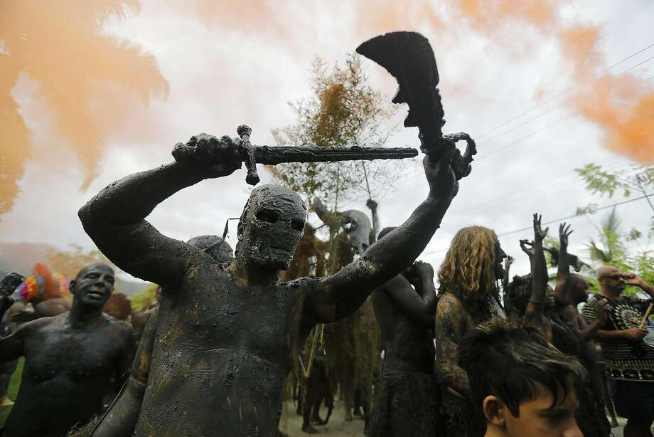 "Mud covered revelers attend the ""Bloco da Lama"" or ""mud street party"" underneath a hazy sky and orange smoke caused by smoke bombs thrown by revelers, in Paraty, Brazil, Saturday, March 1, 2014. Costumes are the name of the game at most of Rio de Janeiro's nearly 500 raucous Carnival street parties, with revelers dressed up as everything from devils to firefighters to sexy angels. But at the Bloco da Lama street celebration in the coastal resort town of Paraty, swamp monster is the acceptable disguise.  Photo: Nelson Antoine, Associated Press"