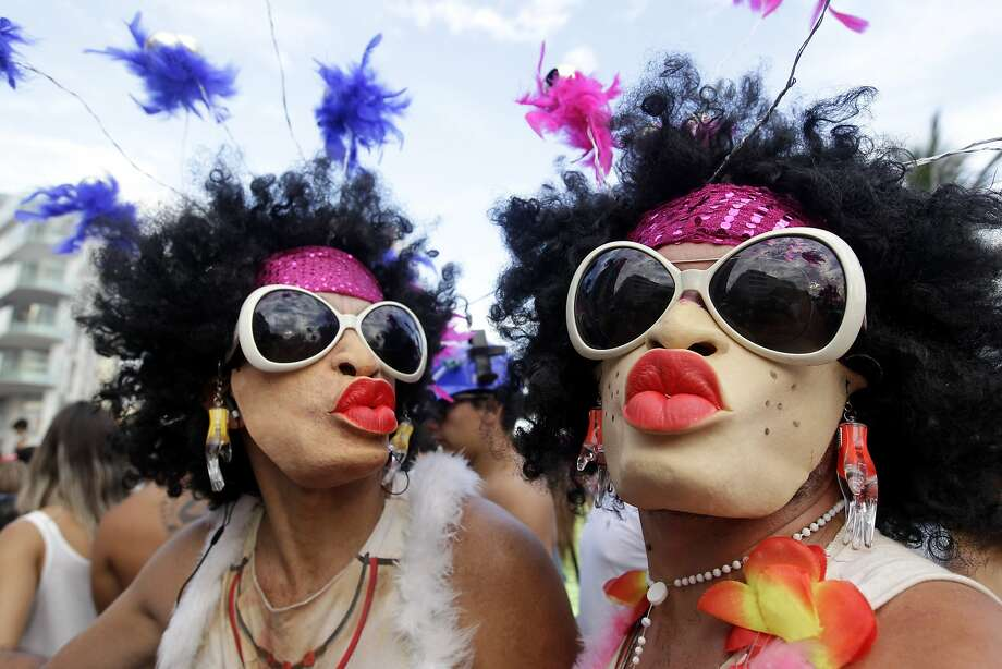 Mask-wearing revelers pose for a photo during the the Banda de Ipanema Carnival parade in Rio de Janeiro, Brazil, Saturday, March 1, 2014. Streets across Brazil have been swamped with Carnival revelers, with the largest parties attracting more than 1 million merrymakers.  Photo: Silvia Izquierdo, Associated Press
