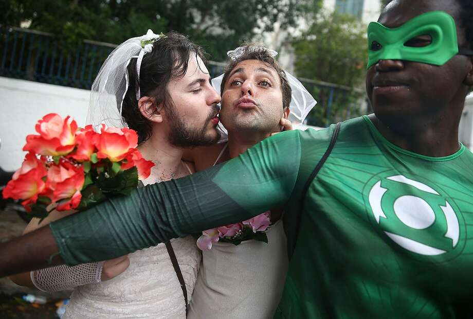 Revelers kiss while posing during the 'Ceu na Terra' street carnival bloco on March 1, 2014 in Rio de Janeiro, Brazil. Carnival is the grandest holiday in Brazil, annually drawing millions in raucous celebrations. Photo: Mario Tama, Getty Images