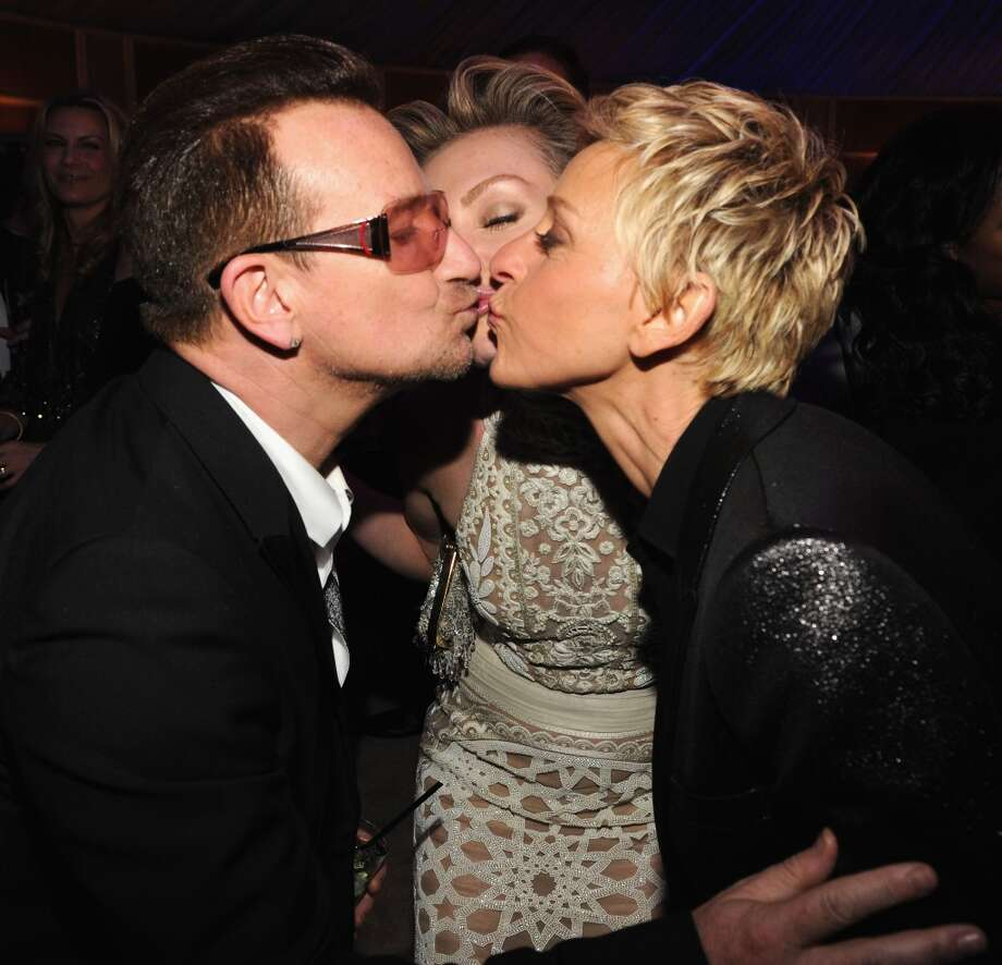 Bono, Portia de Rossi and Ellen  DeGeneres smooch at the 2014 Vanity Fair Oscar Party Hosted By Graydon Carter on March 2, 2014 in West Hollywood, California. Photo: Kevin Mazur/VF14, WireImage