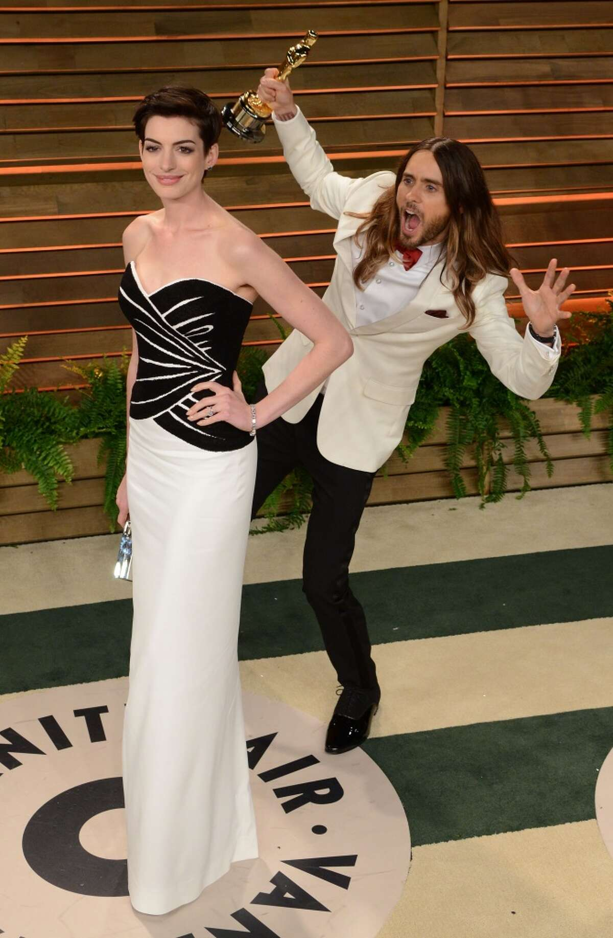 Actress Anne Hathaway gets photobombed by Jared Leto arrive at the 2014 Vanity Fair Oscar Party Hosted By Graydon Carter on March 2, 2014 in West Hollywood, California.