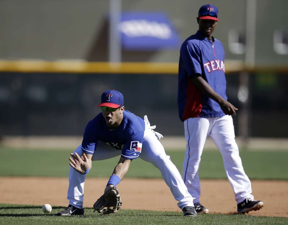 Seattle Seahawks quarterback Russell Wilson, left, fields a ground ball as Texas Rangers second baseman Jurickson Profar, right, stands near during spring training baseball practice, Monday, March 3, 2014, in Surprise, Ariz. (AP Photo/Tony Gutierrez) Photo: Tony Gutierrez, AP