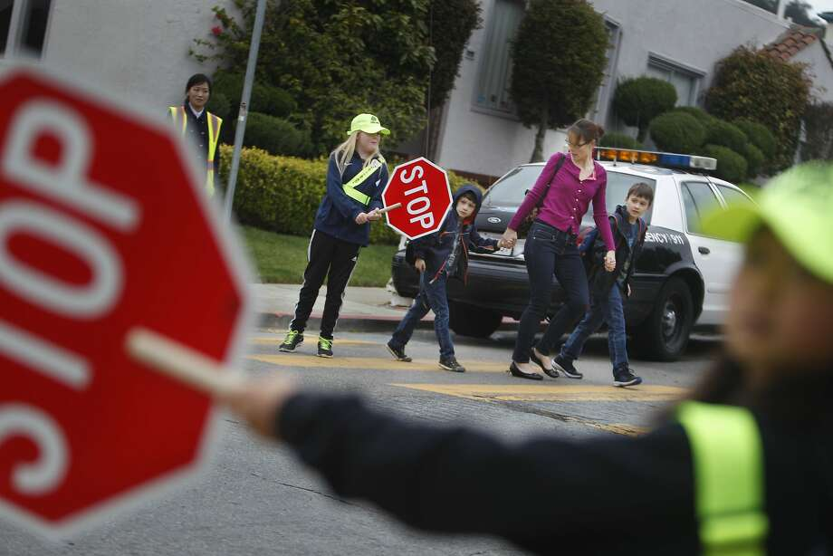 Commodore Sloat Elementary School fifth-graders Ava Mear and Grace Loia-Lopez hold stop signs as Shawna Zimmer crosses with her sons, Ezra and Corbin. The students are learning how to serve as crossing guards, part of a pedestrian safety program led by police, school officials and Supervisor Norman Yee. Photo: Lea Suzuki, The Chronicle