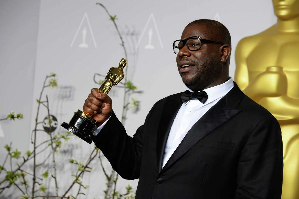 Director Steve McQueen poses in the press room with the award for best picture for