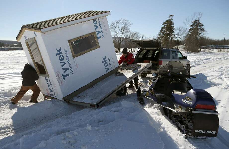 Pack a shack:Eric Marquardt puts his shoulder into his ice shack as he and Jeff Schaefer 