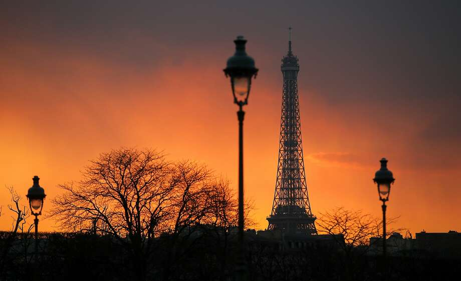 The sky glows behind the Eiffel tower at sunset in Paris. Photo: Lionel Cironneau, Associated Press