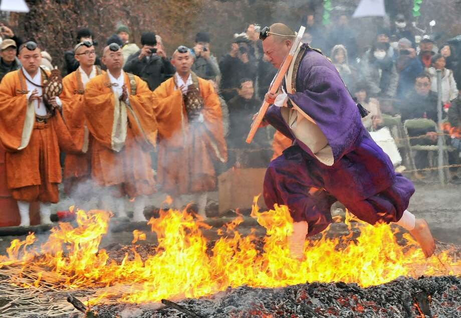 Tortured soles:A Buddhist devotee dashes barefoot through flames during the Nagatoro 