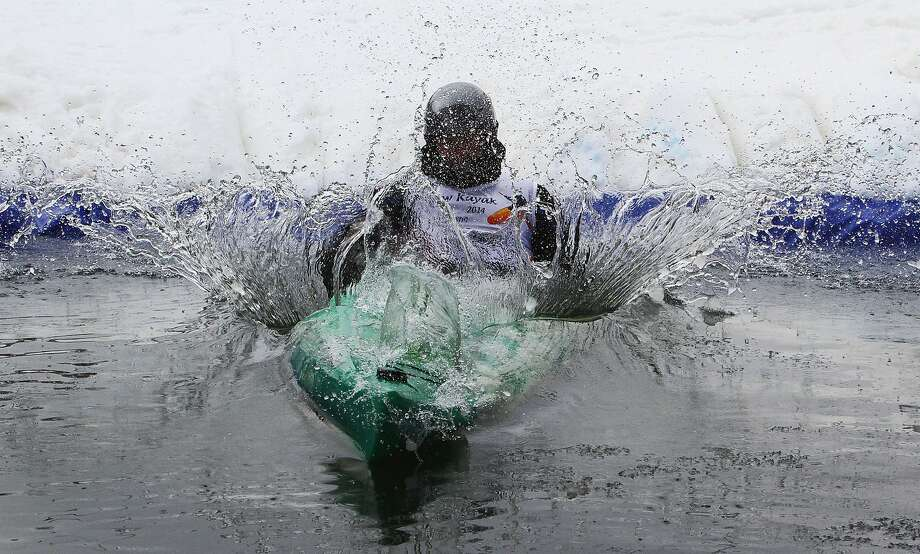 Slide and splash: A kayaker hits the pond at the bottom of an alpine skiing track during 