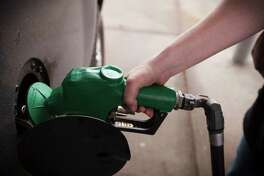 **EMBARGO: No electronic distribution, Web posting or street sales before Monday 12:01 a.m. ET March 3, 2014. No exceptions for any reasons. EMBARGO set by source.* Lila Holmes pumps diesel fuel into her truck at a gas station in Texas City, Texas, Feb. 25, 2014. The Environmental Protection Agency plans to unveil a major new regulation on March 3 that forces oil refiners to strip out sulfur, a smog-forming pollutant linked to respiratory disease, from American gasoline blends, according to people familiar with the agency's plans.