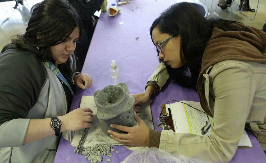 Natalie Garza, 15, gets instruction from Ashley Perez, visual arts high school instructor at SAY Sí, last week. The nonprofit, now in its 20th year, provides programs to help students develop artistic and social skills. Photo: Helen Montoya / San Antonio Express-News / ©2013 San Antonio Express-News