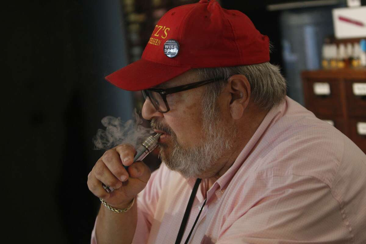 Andy Michelson vapes on an e-cigarette while working at the Vapor Den on Monday, March 3, 2014, in San Francisco, Calif.