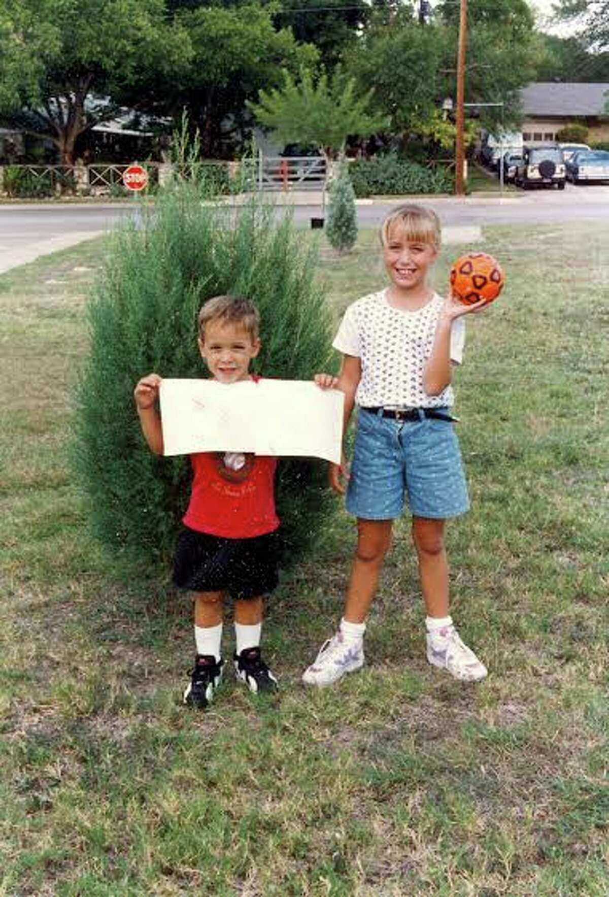 Then: Siblings Brian Bowles (age 5) and Emily Bowles (age 9) pose at Colonies North Elementary School in 1996 in front of two Arizona cypress trees planted by Emily four years earlier, when she was in kindergarten.