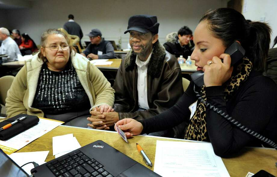 Carole, 58, and Rufus, 62, Youngblood, of Bethel, Conn., work with Erika Calderon of Danbury, to sign up for Access Healthcare Connecticut at the Danbury Library, Monday, March 3, 2014. Photo: Carol Kaliff / The News-Times
