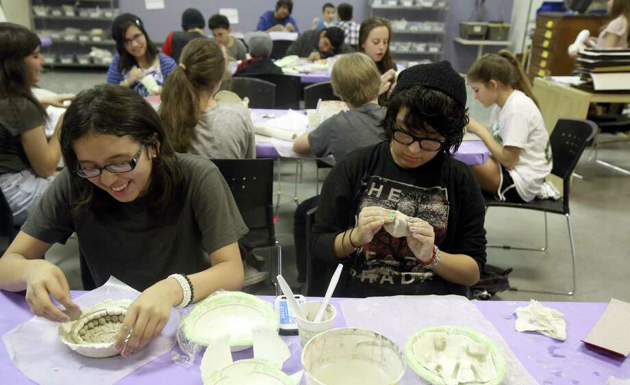 Gabriela Rodriguez (left) and Miranda Gutierrez, both 13, try their hands at sculpting. A nonprofit, SAY Sí helps students develop artistic and social skills. Photo: Photos By Helen L. Montoya / Conexión / SAN ANTONIO EXPRESS-NEWS