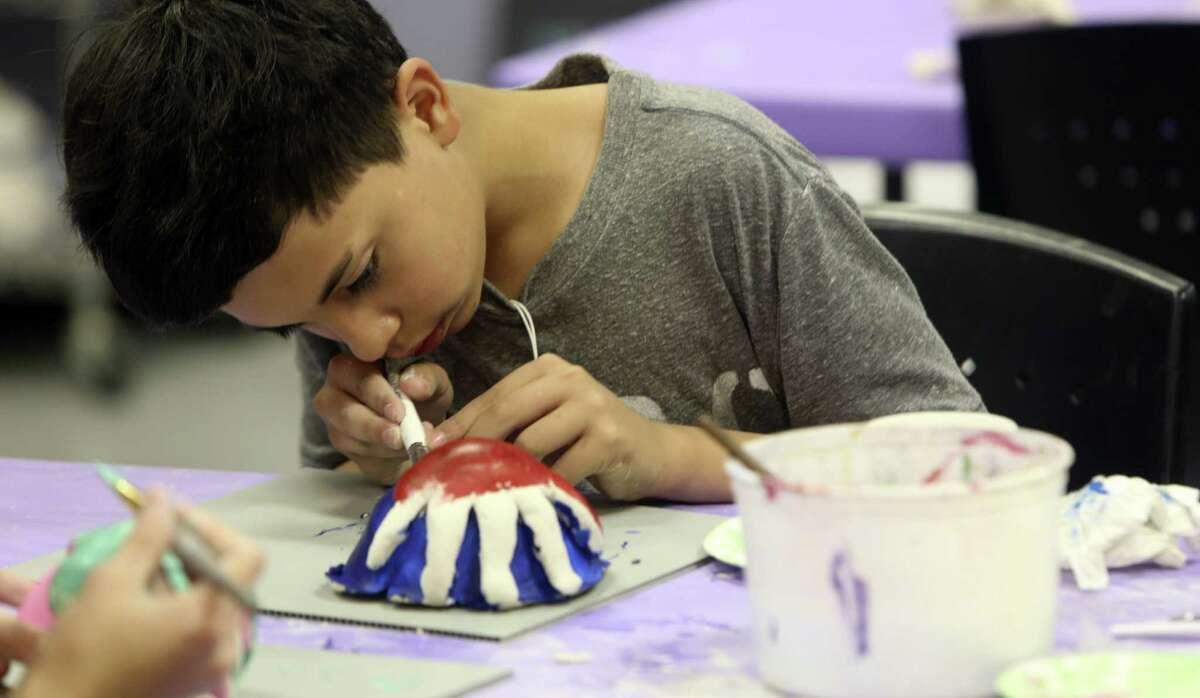 Arturo Botello, 13, a middle school student in SAY Sí's Working Artist and Mentors program, creates with clay. The program allows high school junior and seniors a chance to mentor younger students.