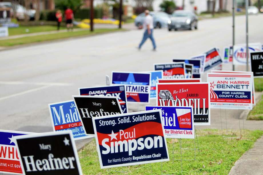 A man walks by candidates' signs during early voting at the City of Houston Metropolitan Multi-Service CenterTuesday, Feb. 18, 2014, in Houston. (Cody Duty / Houston Chronicle) Photo: Cody Duty, Staff / © 2014 Houston Chronicle