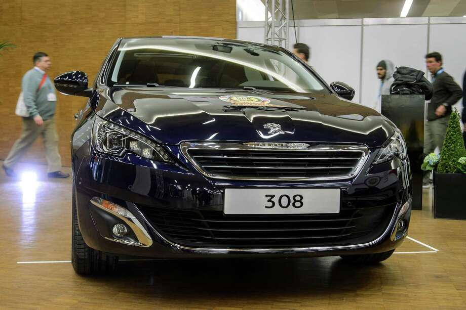 "This picture taken on March 3, 2014 shows a Peugeot 308 car displayed after it has awarded the ""Car of the year 2014"" award on the eve of the press day of the Geneva Motor Show in Geneva. Despite their continued hardship, French carmakers should play a more central role at this year's Geneva Motor Show, where smaller city cars are expected to get more attention than previously. Photo: FABRICE COFFRINI, AFP/Getty Images / 2014 AFP"
