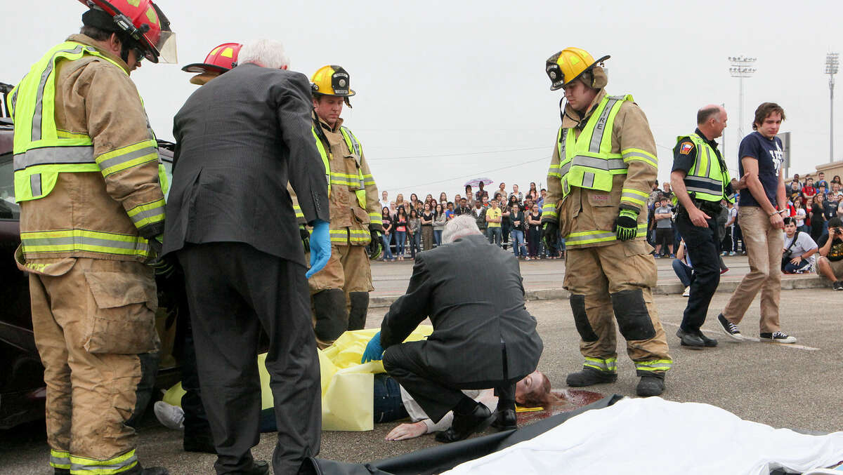 Clemens students watch as Tate Gibson, right, portraying the driver responsible for a fatal accident, is escorted to jail while Berkley Irwin, center, depicting a deceased victim, is about to be taken to the morgue.